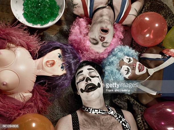 Overhead view of three adults wearing clown face paint and wigs with blow up doll
