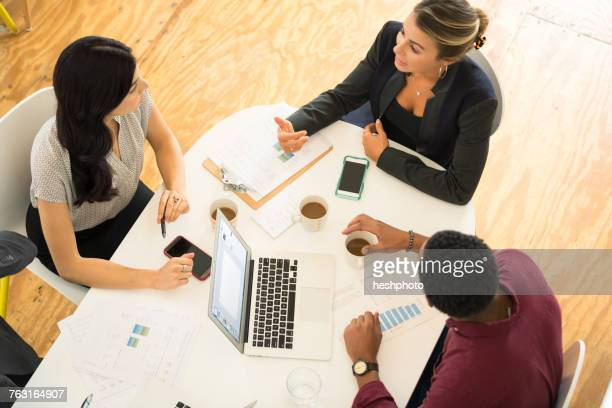 Overhead view of three businesswomen and men meeting at office table