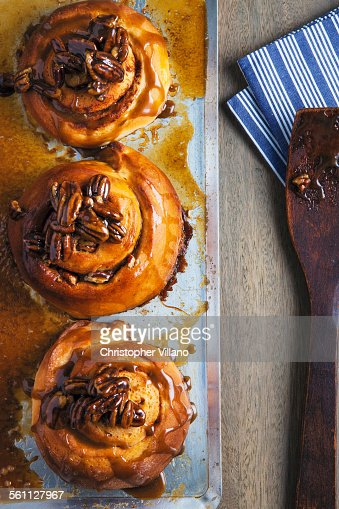 Overhead view of three sticky buns on baking tray
