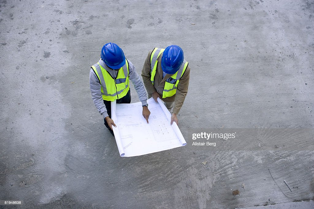 Overhead view of two building workers looking at construction plans : Stock Photo
