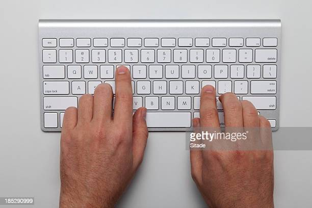 Overhead view of two hands on a keyboard