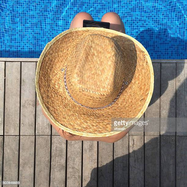 Overhead view of Woman with digital tablet sitting at the edge of swimming pool