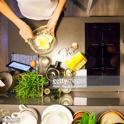 Overhead view of womans hands stirring eggs in mixing bowl