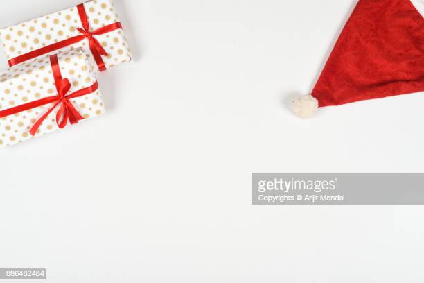 Overhead view of wrapped gift boxes, Santa cap for Christmas gifts white background