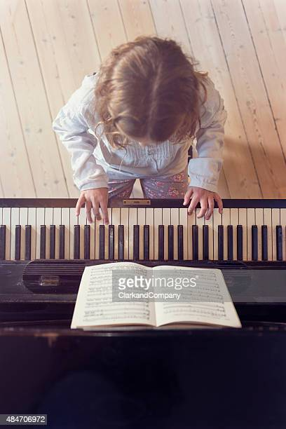 Overhead View of Young Girl Playing Piano In Sunlight Room