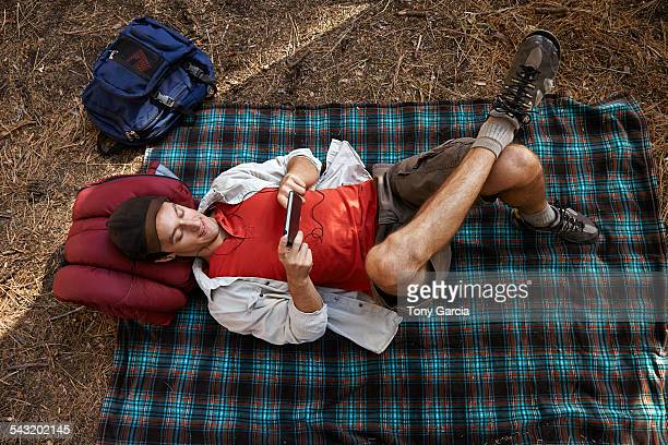 Overhead view of young male camper lying on picnic blanket in forest, Los Angeles, California, USA