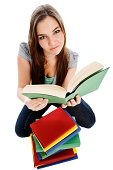 Overhead view of young woman looking up from book pile
