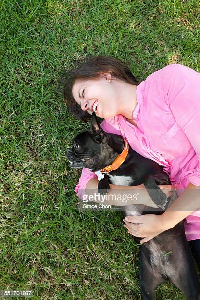 Overhead view of young woman lying in park playing with dog