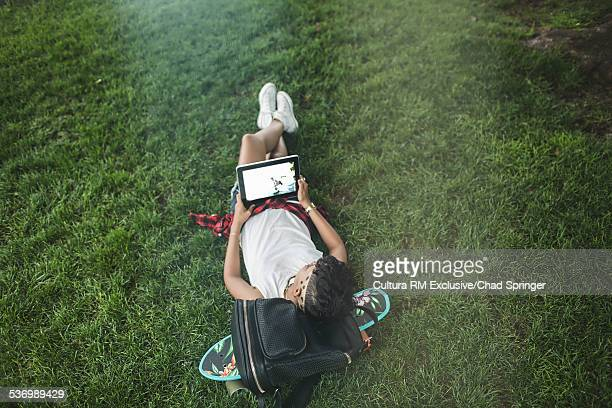 Overhead view of young woman skateboarder lying in park looking at digital tablet