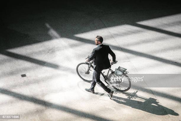 overhead view on elegant businessman going with bycicle in city