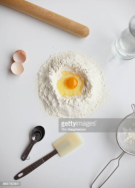 Overhead view with raw egg in center of flour stack and kitchen utensils