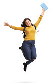 Overjoyed female student with a backpack and a book jumping and gesturing happiness isolated on white background