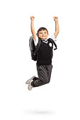 Overjoyed schoolboy jumping and gesturing happiness isolated on white background