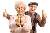 Overjoyed seniors holding their thumbs up isolated on white background