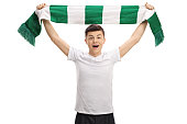 Overjoyed teenage football fan holding a scarf isolated on white background