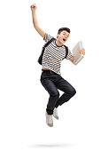 Overjoyed teenage student jumping and gesturing happiness isolated on white background