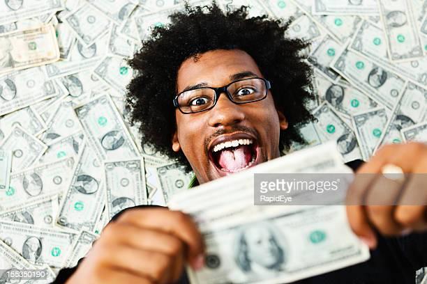 Überglücklich junger Mann, umgeben von US-Dollar