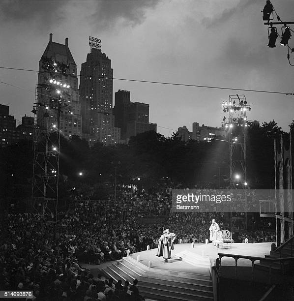 Overlooking actors performing on stage under floodlights in Central Park at the opening night of the Shakespeare festival in New York | Location...
