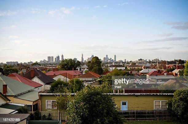 Overlooking suburban roofs towards a city skyline