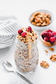 Overnight oats with berries and nut butter in jar. Healthy breakfast. Vegan, vegetarian and weight loss diet concept