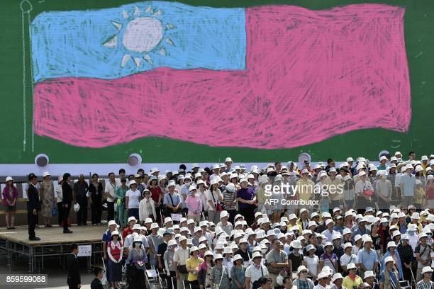 Overseas Taiwanese stand in front of an image of the Republic Of China flag while taking part in a National Day ceremony in Taipei on October 10 2017...