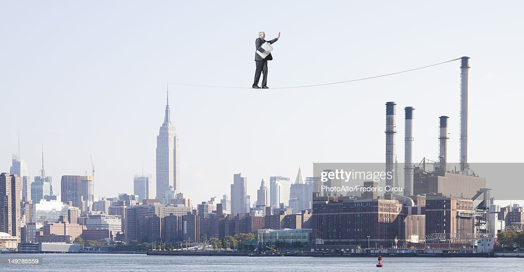 Oversized businessman walking on tightrope above city, carrying briefcase stuffed with cash