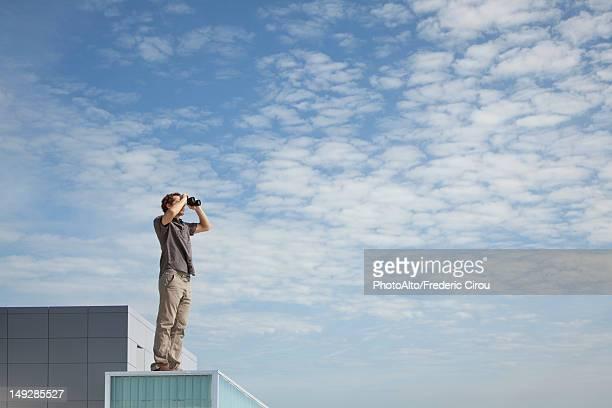 Oversized man standing on rooftop, looking through binoculars