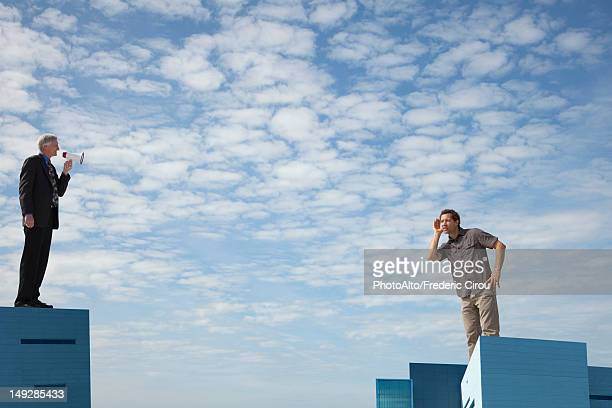 Oversized men standing on rooftops, one speaking through megaphone
