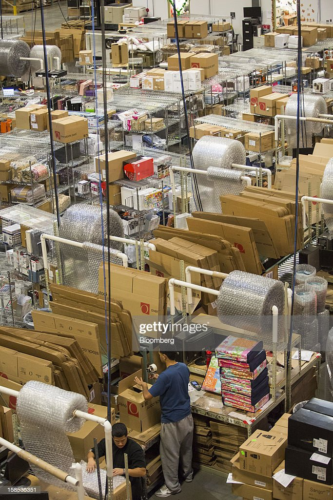 Overstock.com Inc. employees pack orders during one of the busiest days prior to Christmas at the company's distribution center in Salt Lake City, Utah, U.S., on Tuesday, Dec. 18, 2012. Online sales may grow to a record $43.4 billion in the last two months of the year, a 17 percent increase from last year, according to ComScore Inc. Photographer: Ken James/Bloomberg via Getty Images