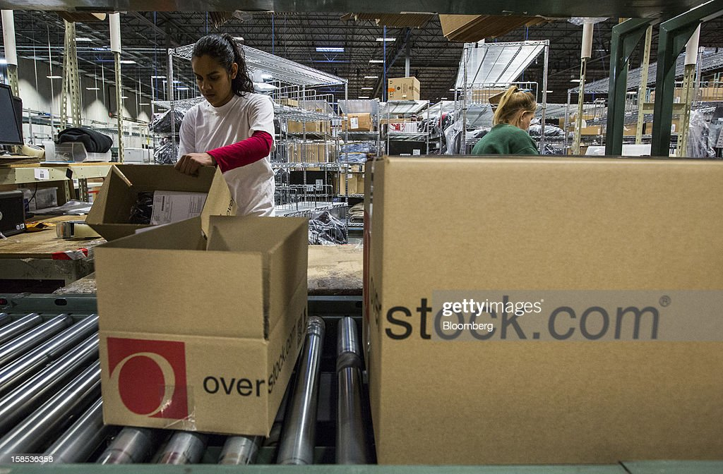 Overstock.com Inc. employees Patricia Aparicia, left, and Lou Perterson pack orders at the company's distribution center in Salt Lake City, Utah, U.S., on Tuesday, Dec. 18, 2012. Online sales may grow to a record $43.4 billion in the last two months of the year, a 17 percent increase from last year, according to ComScore Inc. Photographer: Ken James/Bloomberg via Getty Images