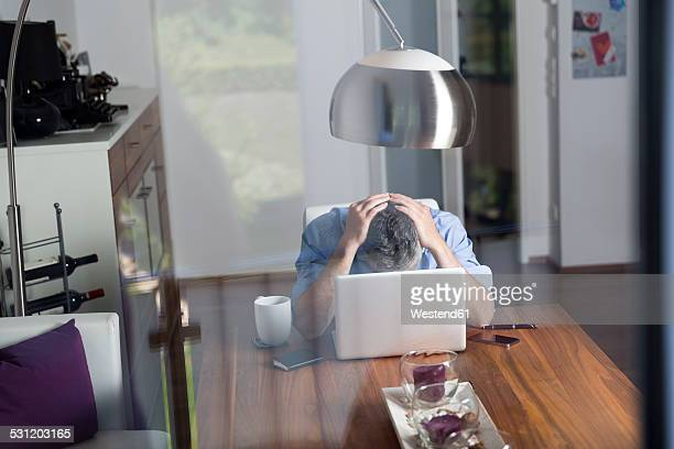 Overstressed businessman with head in his hands sitting at his home office