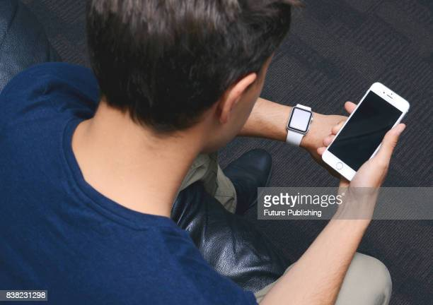 Overtheshoulder view of a man using an Apple iPhone 6 smartphone and Apple Watch taken on May 12 2015