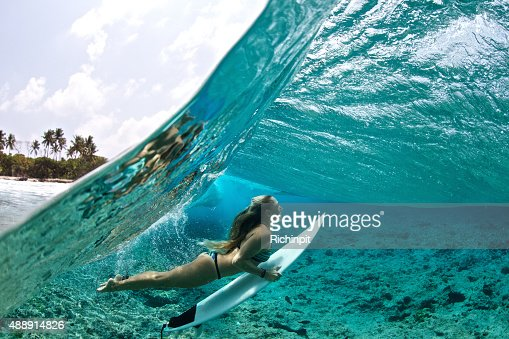 Over/under of surfer girl duck diving tropical waves