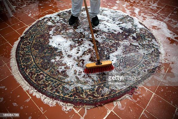 Overview of carpet cleaning worker scrubbing circular carpet
