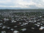 Overview of Refugee Camp near Goma, Kivu Province, Republic of Congo Africa which is built on a recent volcanic lava field where there are no trees or other amenities.  Refugees which have come over t