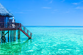 Overwater Bungalow in the lagoon turquoise water. Maldives, tropical island.