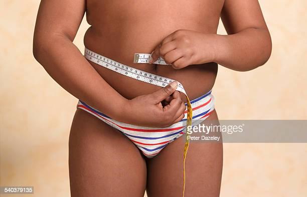 Overweight boy measuring himself