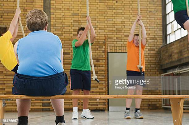 Overweight boy watching others in gym class