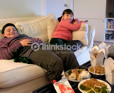 Overweight Brother And Sister Sitting On A Sofa Eating Takeaway Food Watching The Tv