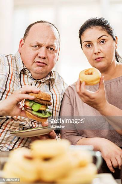 Overweight couple eating unhealthy food.