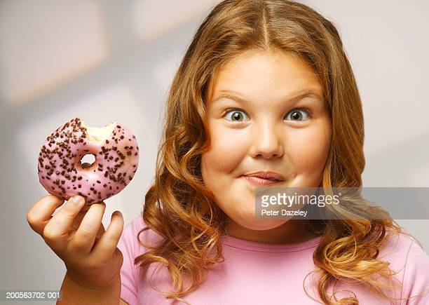 Overweight girl (8-9) eating doughnut, smiling, portrait, close-up