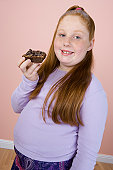 Overweight girl holding brownie, portrait