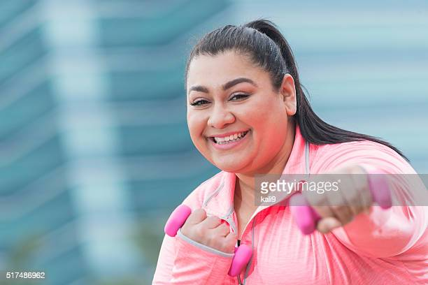 Overweight Hispanic woman exercising with handweights