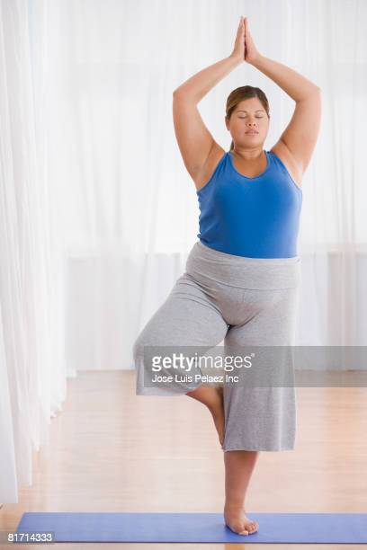Overweight Hispanic woman practicing yoga