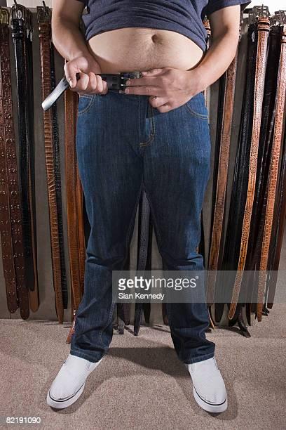 Overweight man adjusting his belt