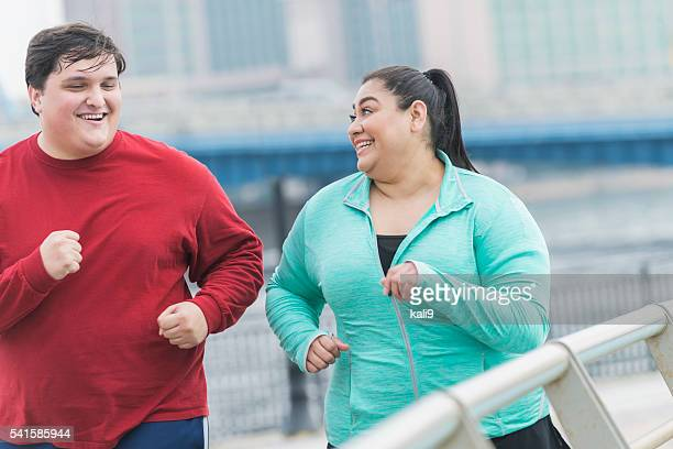 Overweight man and woman jogging in the city