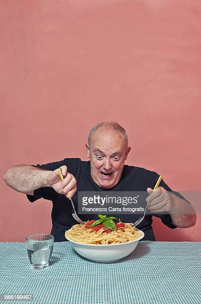 Overweight man eating a plate of spaghetti
