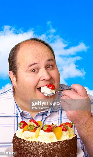 Overweight man enjoying fruit gateau in open air
