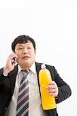 Overweight man holding a large bottle of orange juice