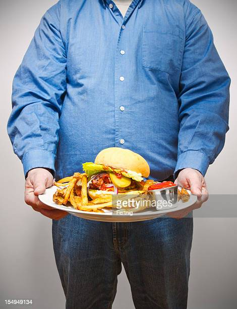 Overweight man holding a very large plate of fried food